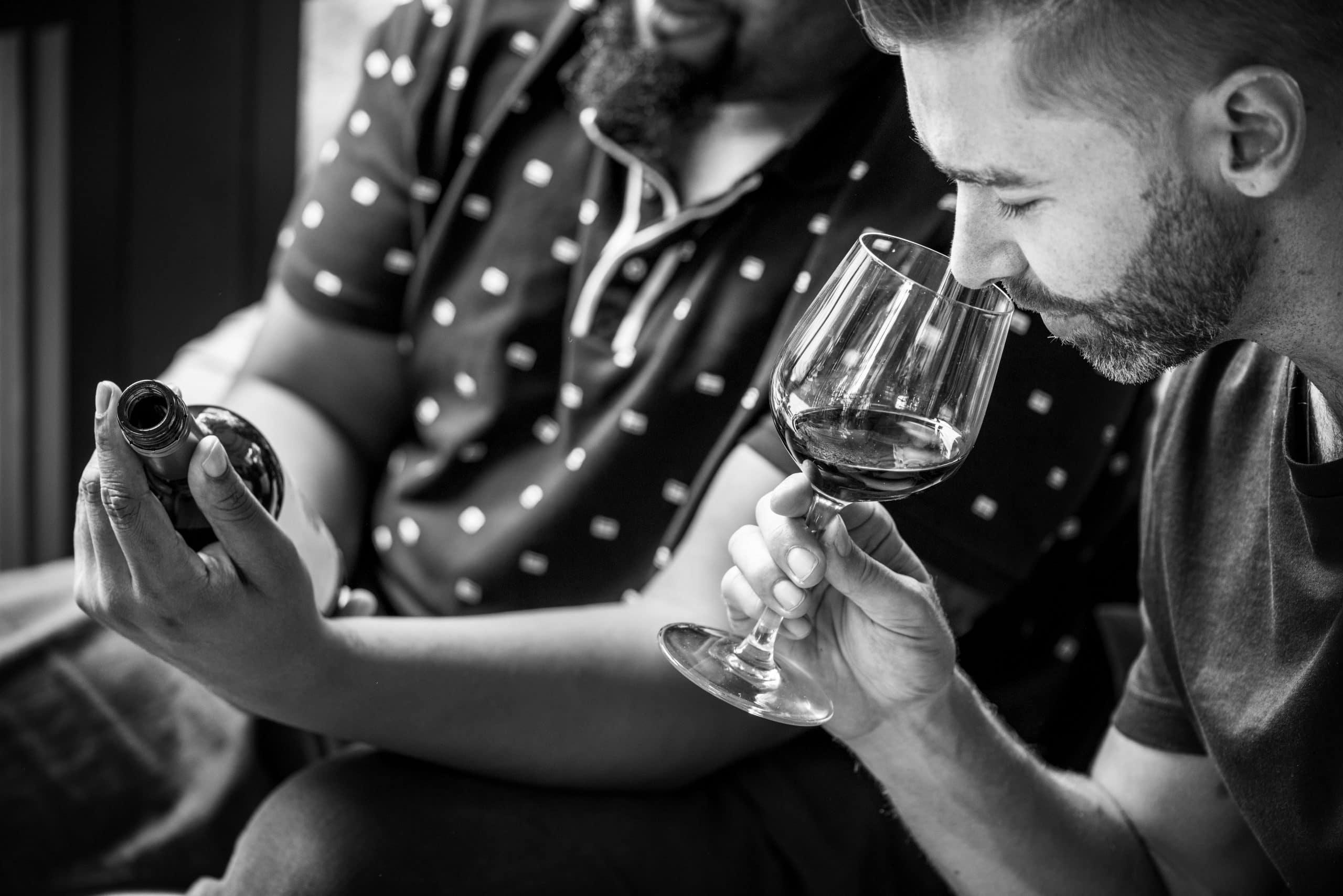 Un homme dégustant du vin avec une autre personne tenant la bouteille