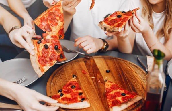 Amis qui mangent une pizza avec des olives