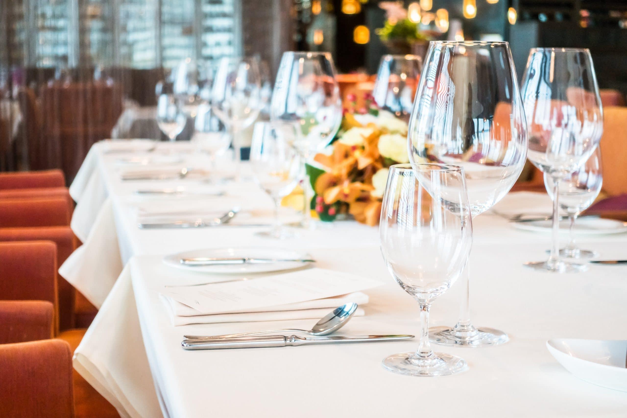 Soirée, diner pour déguster des produits originaux et locaux Table avec verres à vin, couvert, fleurs.