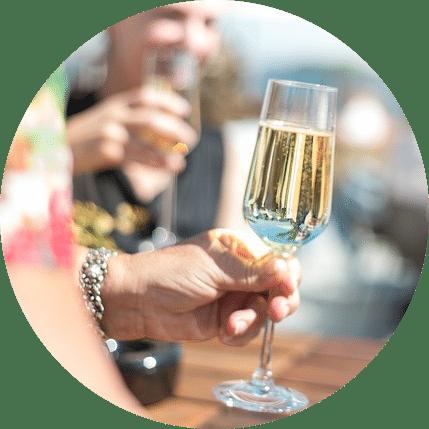 Femme levant son verre de champagne, un homme est en arrière plan levant également son verre de champagne pour trinquer