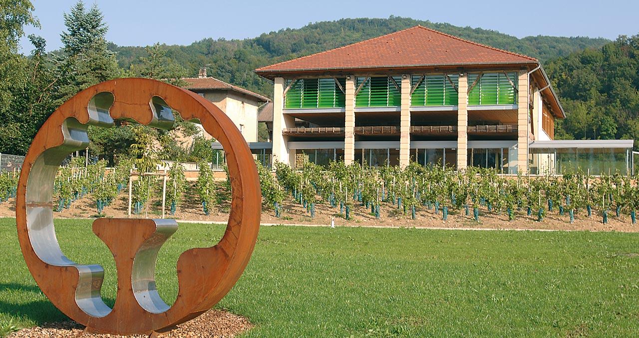 Le Grand Séchoir, musée de la noix à Vinay vu de l'extérieur avec son jardin très vert et ses noyers