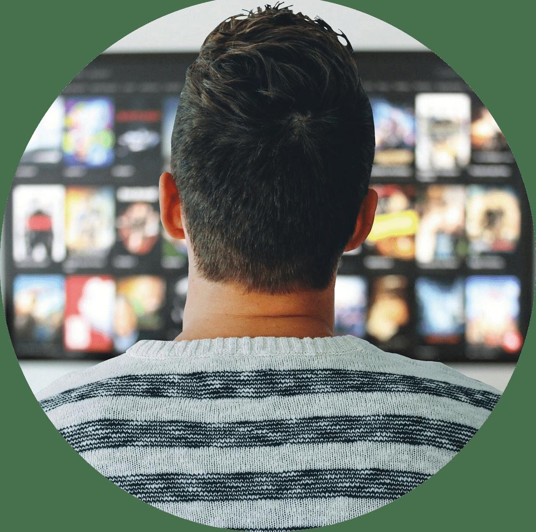 Un homme brun de dos qui regarde Netflix sur l'écran plat de l'hôtel